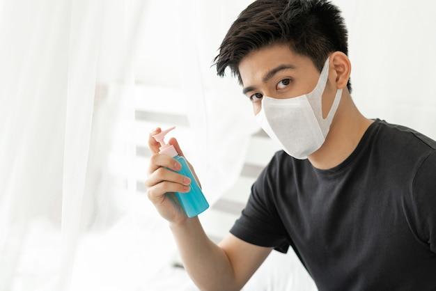 Azjatycki mężczyzna w masce na twarz trzymający alkohol do mycia rąk w celu ochrony koronawirusa covid-19 w pokoju kwarantanny