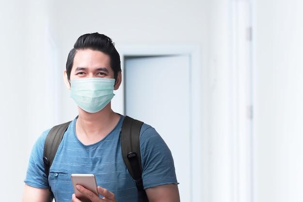 Azjatycki mężczyzna w masce z plecakiem trzymając smartfon w szpitalu. badanie lekarskie przed podróżą