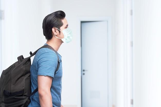 Azjatycki mężczyzna w masce z plecakiem w szpitalu. badanie lekarskie przed podróżą