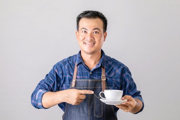 Azjatycki mężczyzna w mundurze baristy trzymając filiżankę kawy