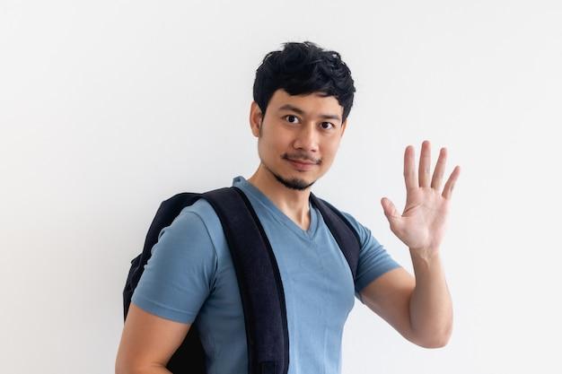 Azjatycki mężczyzna w niebieskiej koszulce z plecakiem macha ręką na na białym tle