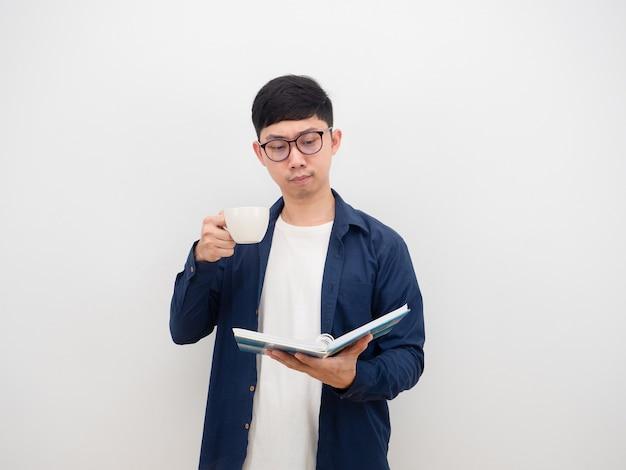 Azjatycki mężczyzna w okularach czyta książkę w ręku i pije filiżankę kawy na białym tle