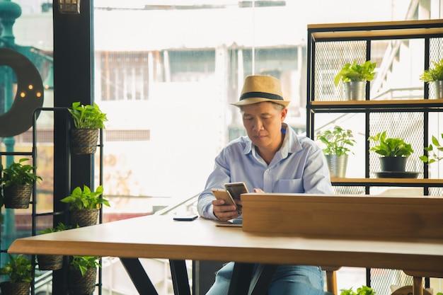 Azjatycki mężczyzna w przypadkowej koszula trzyma dwa telefon komórkowego i wprawiać w zakłopotanie na drewnianym stole przy sklep z kawą