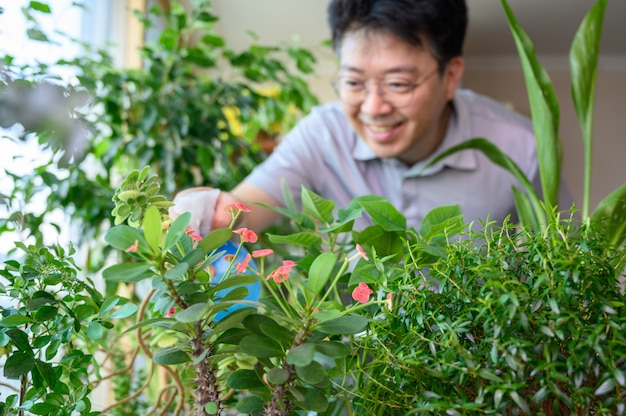 Azjatycki mężczyzna w średnim wieku, który uśmiecha się, dbając o klomb w domu.