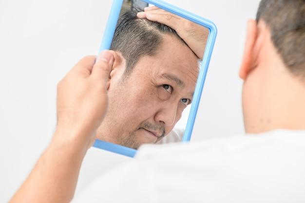 Azjatycki mężczyzna w średnim wieku patrzył w lustro i martwił się wypadaniem lub siwizną włosów na białym tle na białym tle, koncepcja opieki zdrowotnej