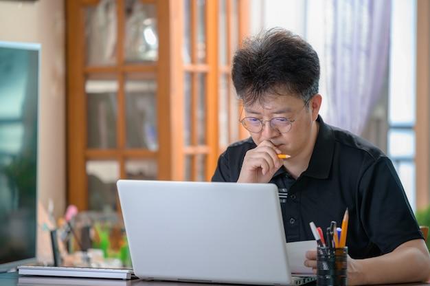 Azjatycki mężczyzna w średnim wieku pracujący w domu. koncepcja telepracy.