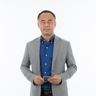 Azjatycki mężczyzna w średnim wieku, ubrany w szarą kurtkę w nieformalnym, swobodnym stylu, trzymający w ręku smartfon i patrząc na kamerę z pewną siebie i małą uśmiechniętą buźką. na białym tle