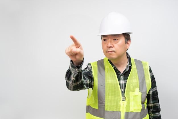 Azjatycki mężczyzna w średnim wieku w jasnozielonej kamizelce roboczej i białym kapeluszu ochronnym.