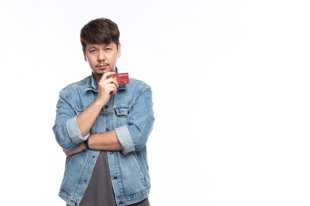 Azjatycki mężczyzna w twarz trochę uśmiech trzymając kartę kredytową i patrzeć na kamery