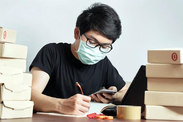 Azjatycki mężczyzna właściciel małej firmy noś maskę pracuj z domu do marketingu online, start-upowego mśp.