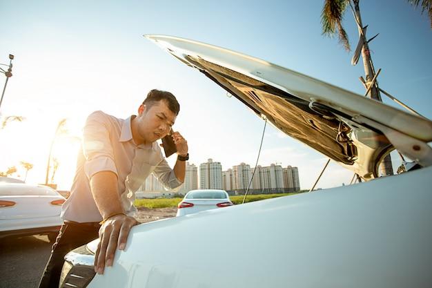 Azjatycki mężczyzna woła o pomoc przez uszkodzony samochód na drodze z lekkim zachodem słońca