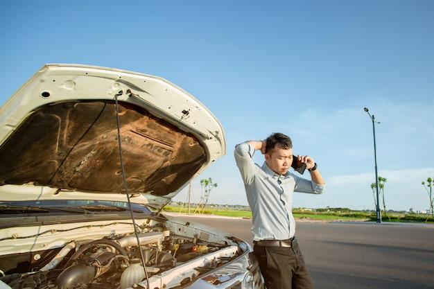 Azjatycki mężczyzna woła o pomoc przez uszkodzony samochód na drodze