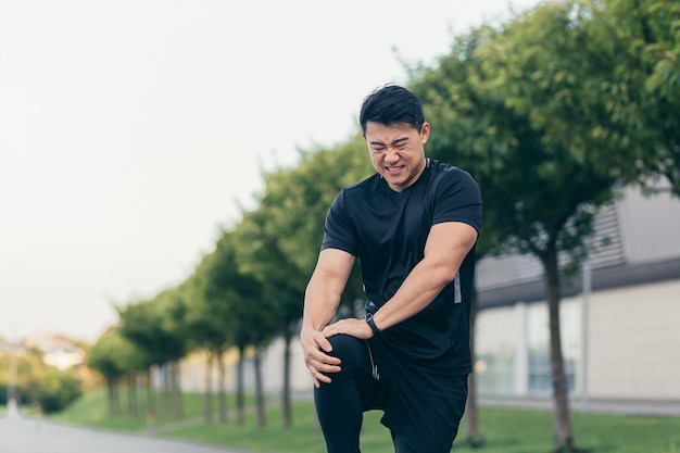 Azjatycki mężczyzna z bólem kolana po bieganiu i fitnessie, silny ból nóg