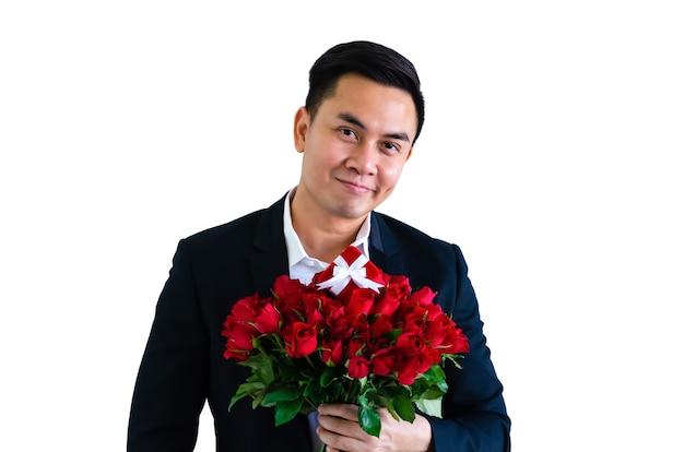Azjatycki mężczyzna z bukietem czerwonych róż i pudełko na walentynki koncepcja.