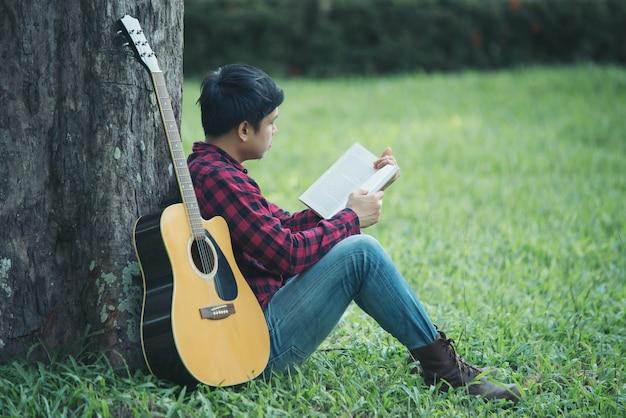 Azjatycki mężczyzna z gitarą akustyczną w parku