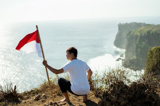 Azjatycki mężczyzna z indonezyjską flagą indonezji na szczycie góry