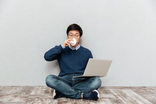 Azjatycki mężczyzna z laptopem i filiżanką. siadać