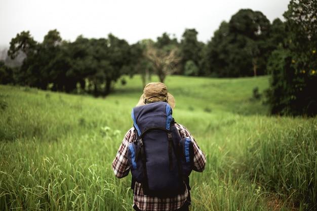Azjatycki mężczyzna z plecakiem i kapeluszem przy górą