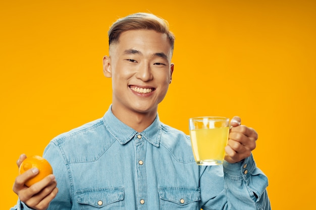 Azjatycki mężczyzna z pomarańczową owoc i herbatą