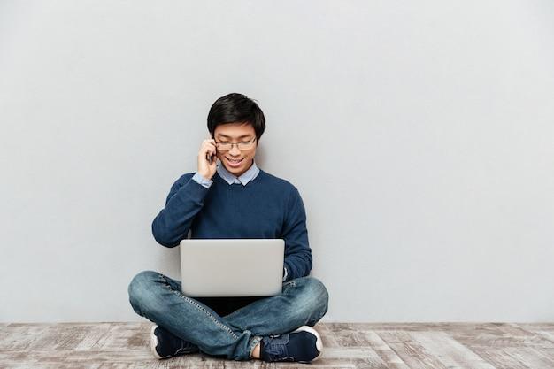 Azjatycki mężczyzna z telefonem i laptopem. siadać