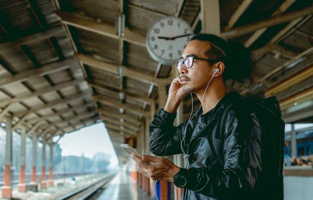Azjatycki mężczyzna z telefonem komórkowym czeka na spóźniony pociąg.