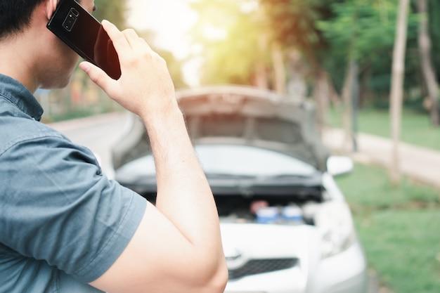 Azjatycki mężczyzna za pomocą telefonu komórkowego dzwoni po pomoc po awarii samochodu na ulicy