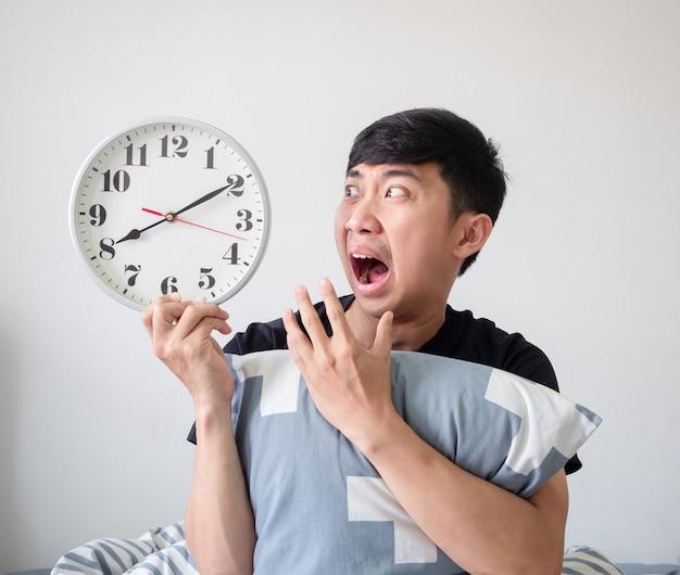 Azjatycki mężczyzna zszokowana twarz i patrząc na zegar w ręku i przytulająca poduszkę budzą późną koncepcję