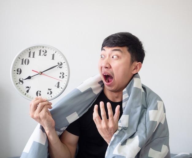 Azjatycki mężczyzna zszokowana twarz i patrząc na zegar w ręku i przytulająca poduszkę na białym na białym tle obudzić się późno