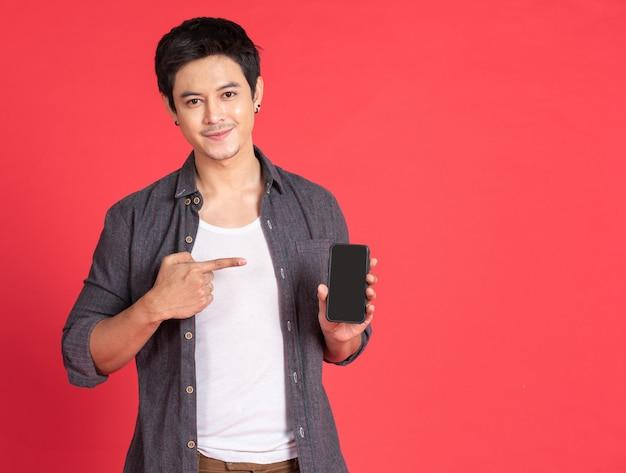 Azjatycki młodego człowieka use smartphone pastylka