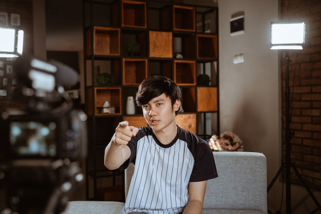 Azjatycki młodego człowieka vlogger nagrywa vlog opowiada kamera