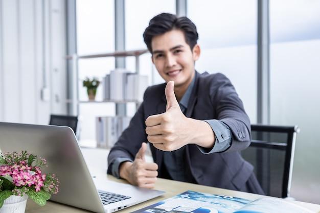 Azjatycki młody biznesmen widzi udany biznesplan na laptopie i papierze dokumentowym abstrakcyjne rozmycie ostrości pokazujące kciuk w górę na drewnianym stole w tle w biurze
