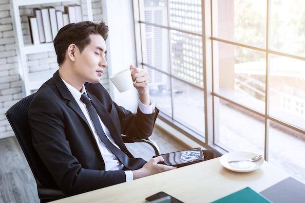 Azjatycki młody biznesmen zobaczyć udany biznesplan trzymający filiżankę kawy, komputer przenośny na tle drewnianego stołu w biurze, biznes wyraził zaufanie embolden.