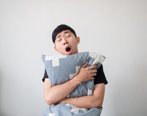 Azjatycki młody człowiek budzi się i przytula poduszkę, ziewa i czuje się senny na białym na białym tle, leniwy koncept
