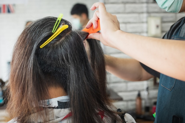 Azjatycki młody człowiek jest cięty nożyczkami z długich włosów do krótkich włosów przez profesjonalnego fryzjera w zakładzie fryzjerskim.