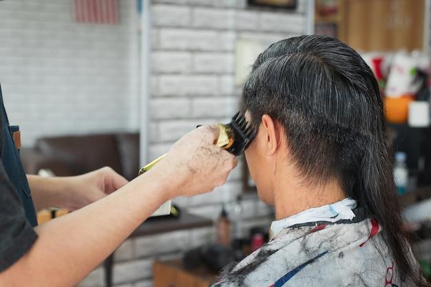 Azjatycki młody człowiek jest cięty z długich włosów na krótkie włosy za pomocą elektrycznej maszynki do strzyżenia przez profesjonalnego fryzjera w zakładzie fryzjerskim.