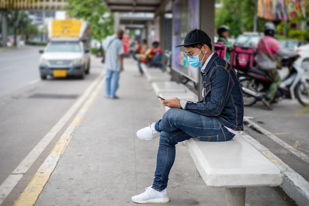 Azjatycki młody człowiek korzystający z inteligentnego telefonu w mieście i noszący maskę na twarz w celu ochrony przed zanieczyszczeniem powietrza, pyłami oraz w celu ochrony przed wirusem grypy, grypą, koronawirusem