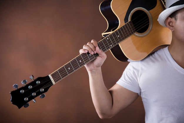 Azjatycki młody człowiek muzyk z gitarą akustyczną