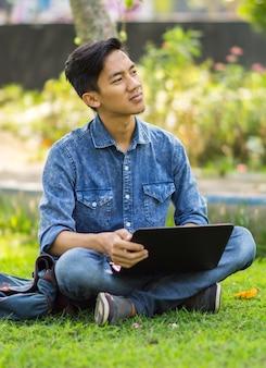 Azjatycki młody człowiek myśli o pomysłach w parku za pomocą laptopa