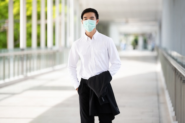 Azjatycki młody człowiek nosi medyczną maskę do ochrony koronawirusa i pm2.5 w tajlandii