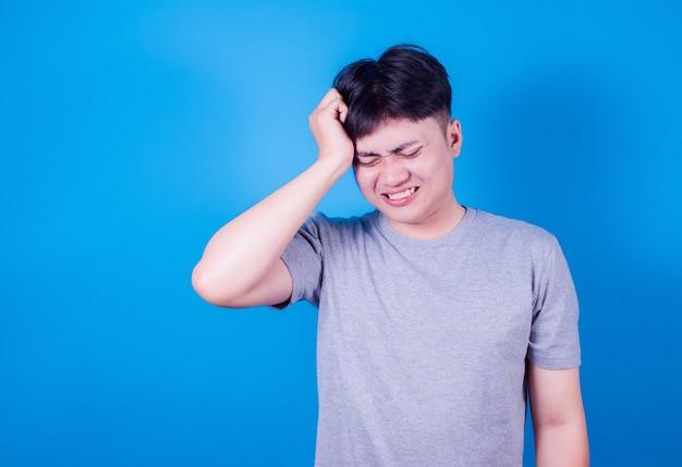 Azjatycki młody człowiek nosi szary t-shirt stojący na niebieskim tle z ręką na ból głowy, ponieważ stres. cierpi na migrenę.