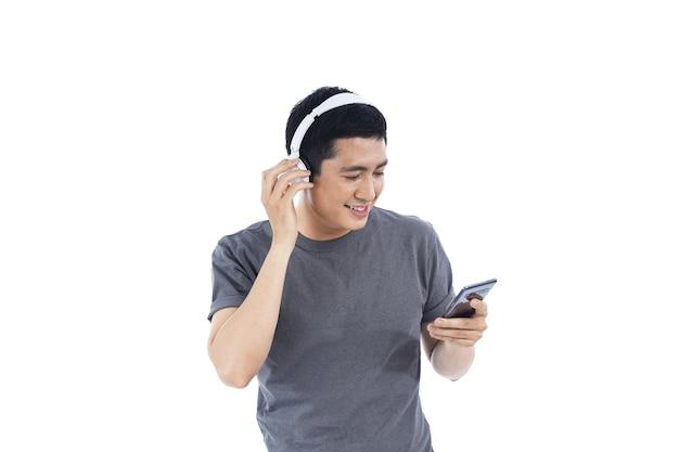 Azjatycki młody człowiek, słuchanie muzyki i śpiewanie w telefonie