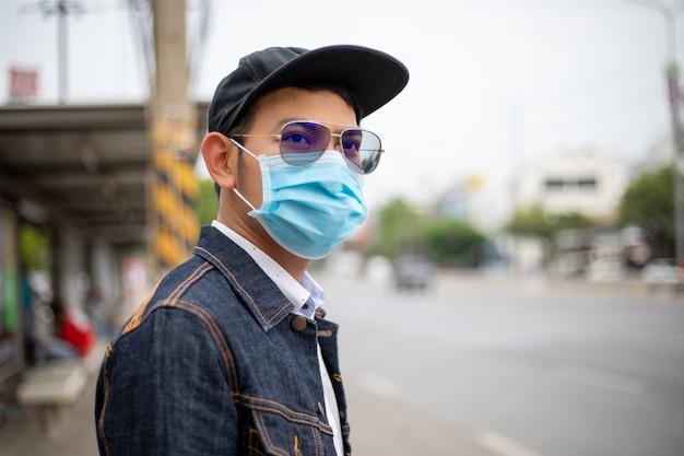 Azjatycki młody człowiek stojący w mieście i noszący maskę ochronną na twarz w celu ochrony przed zanieczyszczeniem powietrza, cząstkami stałymi i ochrony przed wirusem grypy, grypą, koronawirusem w mieście