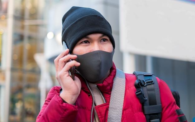 Azjatycki młody człowiek ubrany w maskę ochronną higieny na twarzy podczas przyjmowania telefonu, opieki zdrowotnej i zapobiegania chorobom od koronawirusa, grypy covid19 w zatłoczonym miejscu.