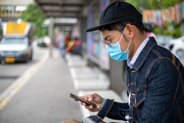 Azjatycki młody człowiek używa mądrze telefon w mieście i jest ubranym twarzy maskę dla ochrony
