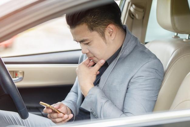 Azjatycki młody człowiek używa telefon komórkowego w samochodzie