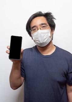 Azjatycki młody człowiek w swobodnej noszeniu chirurgicznej maski medycznej w celu ochrony covid-19 za pomocą inteligentnego telefonu komórkowego na białym tle koncepcja opieki zdrowotnej. zapobieganie epidemii wuana koronawirusa (covid-19) w miejscach publicznych ar