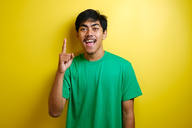 Azjatycki młody człowiek w zielonej koszulce wyglądał na szczęśliwego, myśląc i patrząc w górę, mając dobry pomysł. portret połowy ciała na żółtym tle z miejscem na kopię