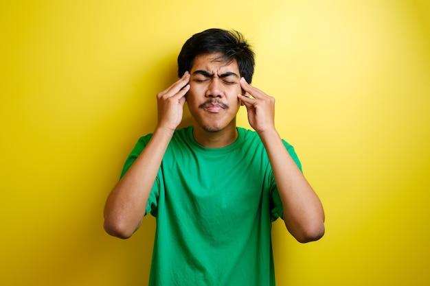 Azjatycki Młody Człowiek Wygląda Na Zdenerwowanego I ściskając Głowy Rękami Z Bólu Głowy. Pojęcie Stresu I Migreny. Premium Zdjęcia