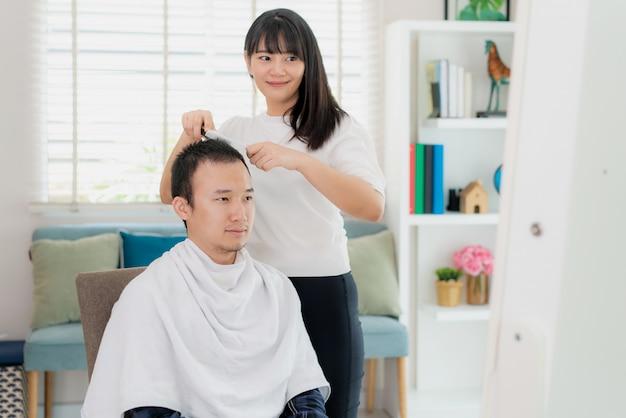 Azjatycki młody człowiek z dziewczyną fryzjerką obcinającą włosy elektryczną maszynką do strzyżenia włosów w domu, pozostają w domu w czasie izolacji domowej od nowego koronawirusa lub covid-19