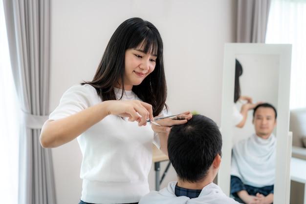 Azjatycki młody człowiek z dziewczyną fryzjerką obcinającą włosy nożyczkami do włosów w domu, pozostają w domu w czasie izolacji domowej od nowego koronawirusa lub covid-19